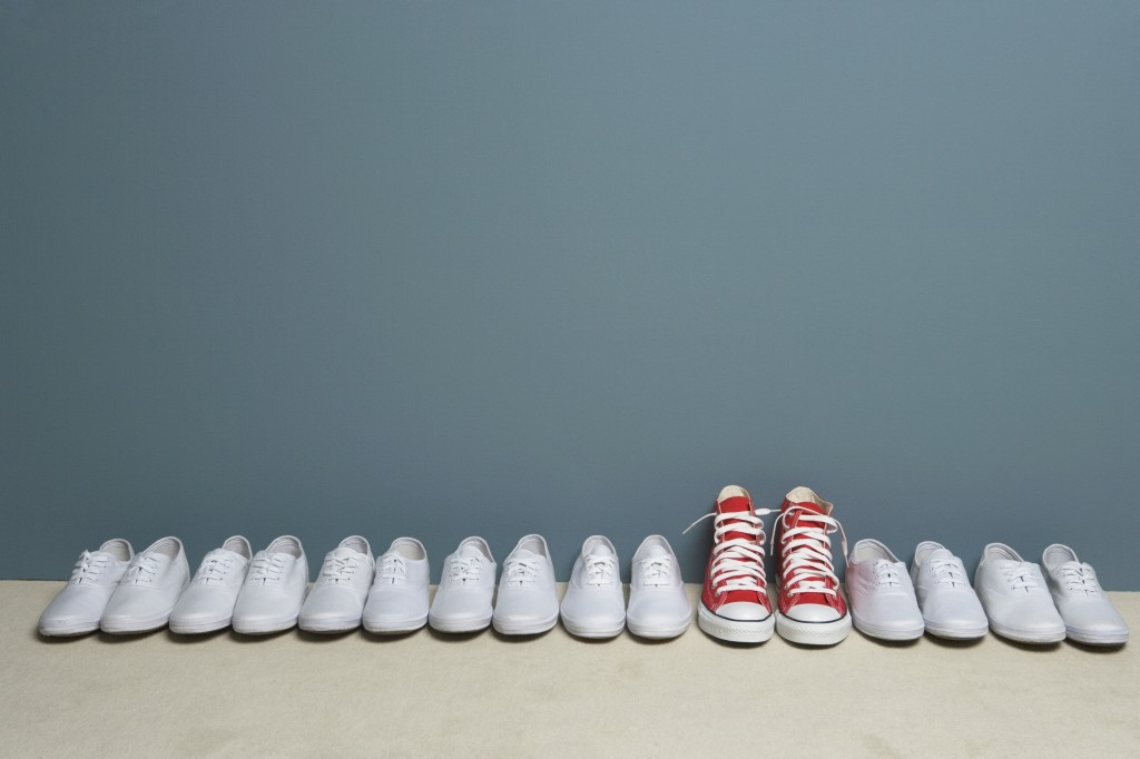 Red converse sneakers stand out from a crowd of white keds